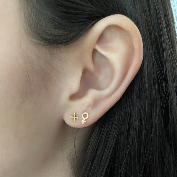 14k gold plus symbol earring and 14k gold venus symbol earring on a woman's ear