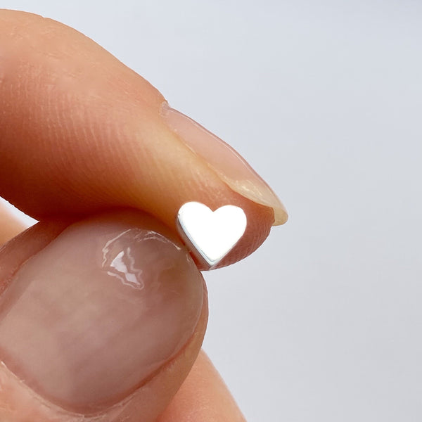 closeup of sterling silver heart stud earring held between a woman's thumb and index finger