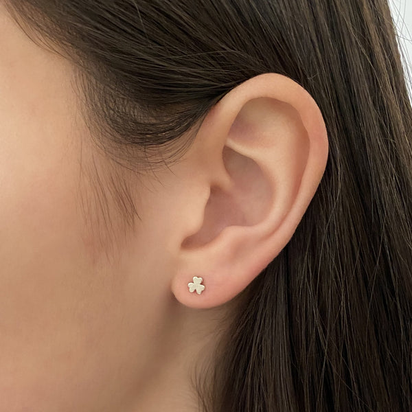 sterling silver shamrock stud earring on a woman's ear