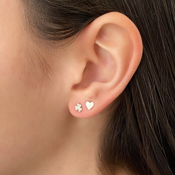 Sterling silver shamrock stud earring and sterling silver heart stud earring on a woman's ear