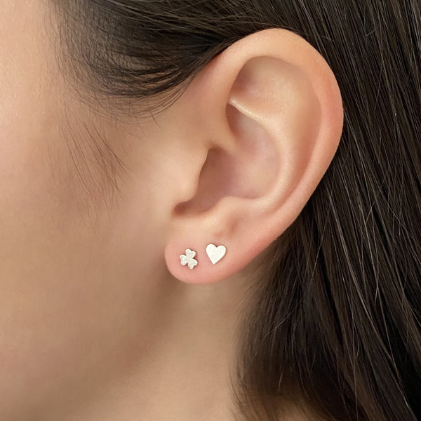 sterling silver shamrock stud earring and sterling silver heart stud earring on woman's ear