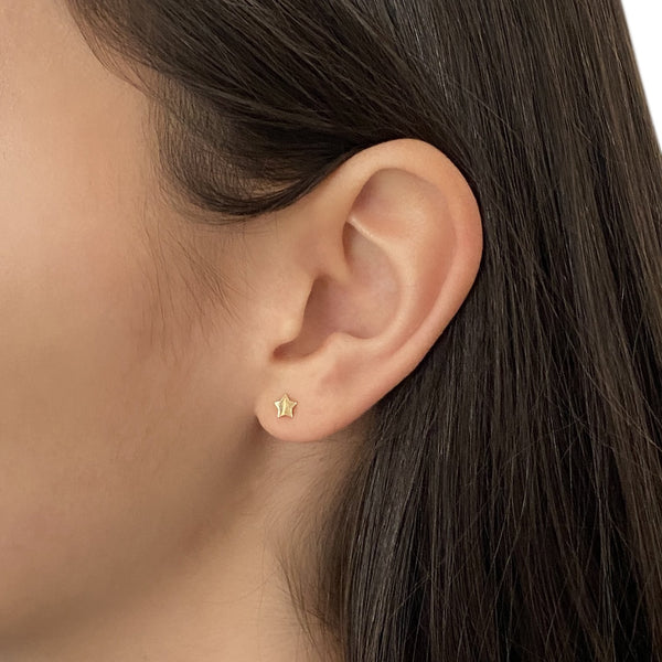 14k gold star stud earring on a woman's ear