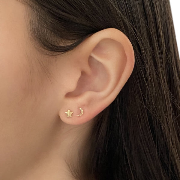 14k gold star stud earring and 14k gold crescent moon stud earring on a woman's ear