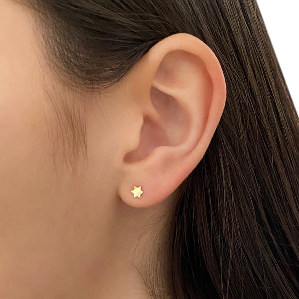 14k gold star of david (or Jewish star) stud earring on woman's ear