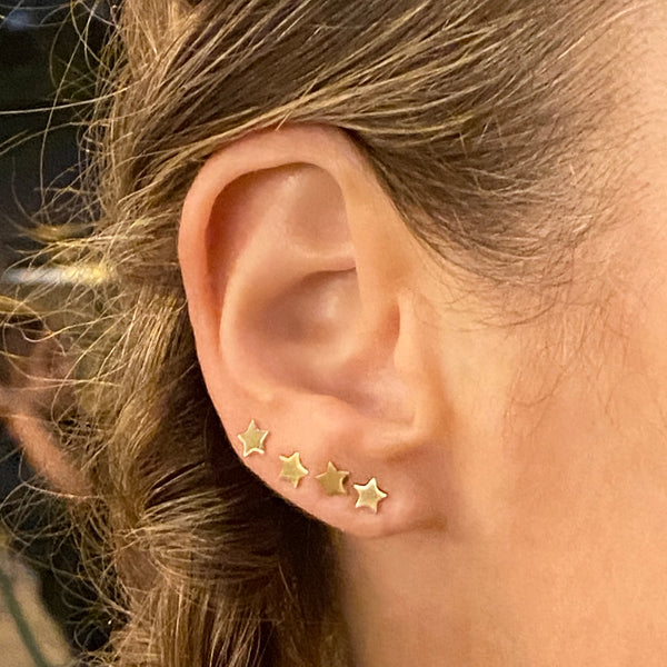 Close up of a woman's ear and she's wearing a 14k yellow gold star stud earring in each of four ear piercings. Some of her light brown hair is visible and it's in a braid.