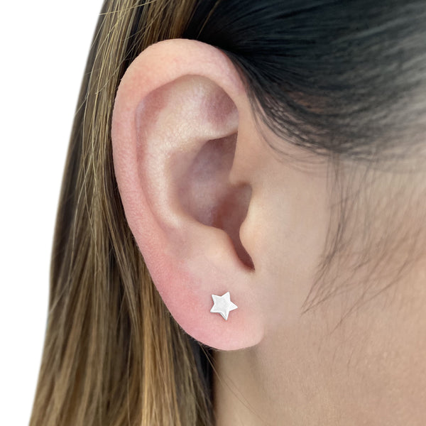 sterling silver star stud earring on a woman's ear