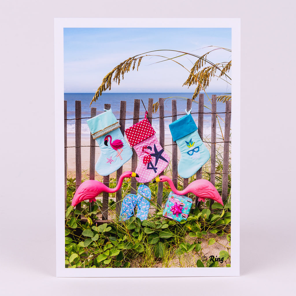 Christmas Notecard with 3 Stockings and Yard Flamingos on Dunes Fence on Beach