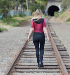 Casual goth clothing is worn while walking on train tracks.