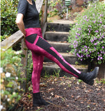 Woman is wearing medium weight stretch cotton knit leggings. The waist is midrise and length goes to ankle. Comes in hand dyed dusty rose red with contrasting black pannels and pockets.