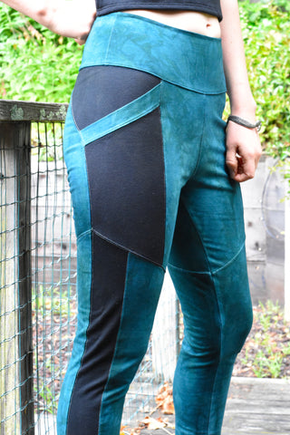 Woman is wearing medium weight stretch cotton knit leggings. The waist is midrise and length goes to ankle. Comes in hand dyed aqua blue with contrasting black pannels and pockets.