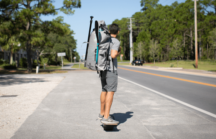 Guy one wheeling with inflatable paddle board travel backpack