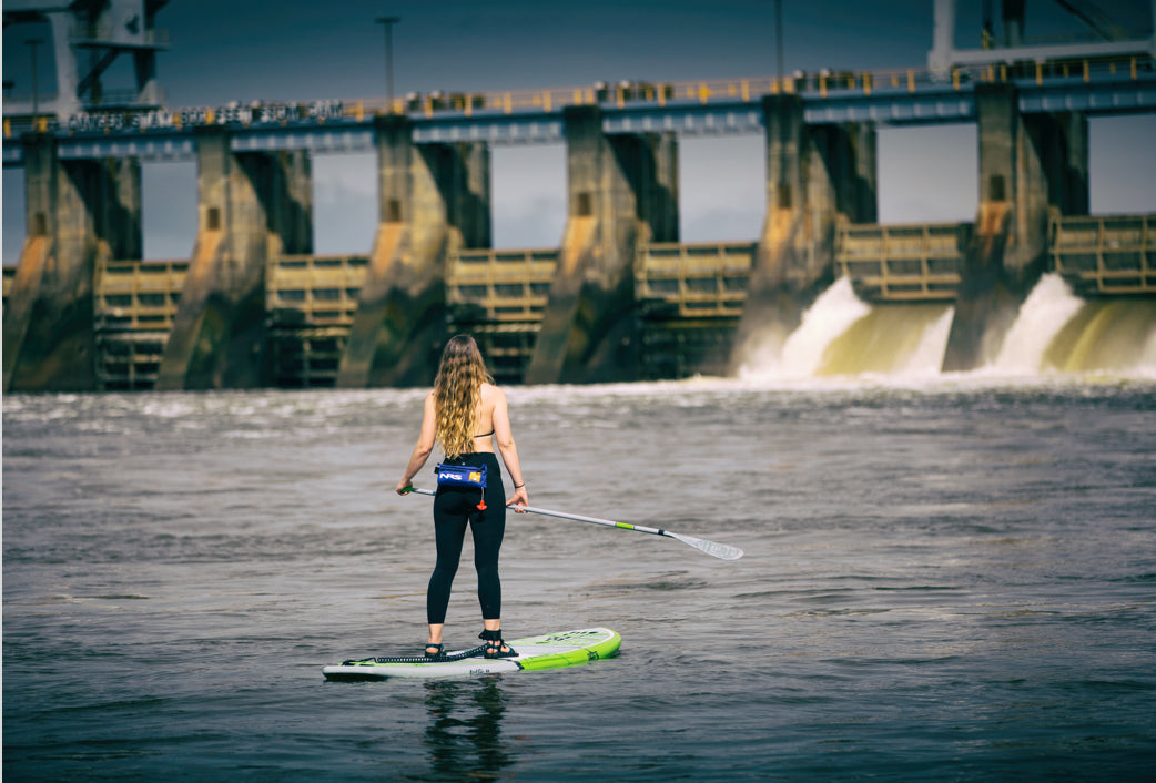 Woman paddling the Chattahoochee River on Gatorshell Flood paddle board with leash and waist life vest