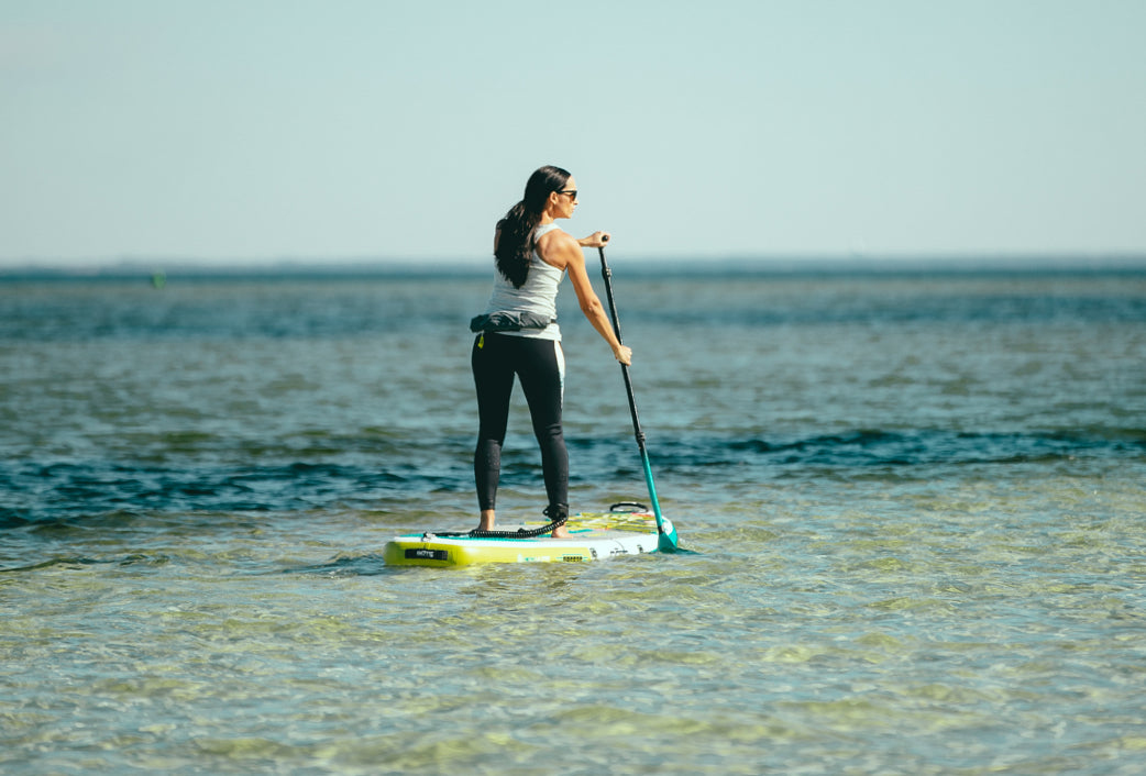 Each paddle stroke should begin in front of your body, pulling the blade back along the side of the board until roughly at the arch of your foot area. Repeat.