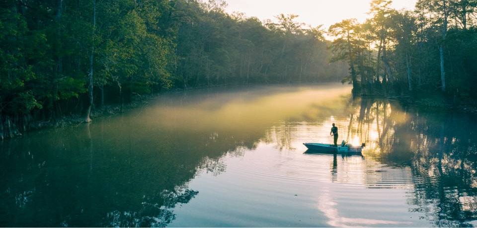 Man stands and fishes from his LONO Aero inflatable kayak in the early sunrise.