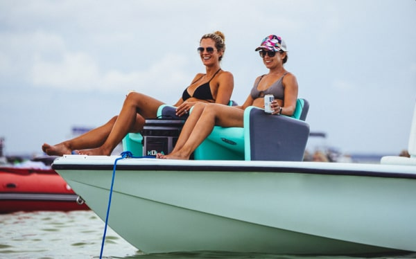Two women sit on BOTE Aero Chairs on the nose of their boat, lounging at the sandbar.
