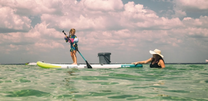 Little girl stand up paddling on a BOTE Flood Aero Full Trax inflatable paddle board.