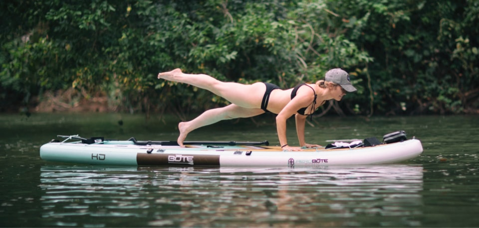 Woman practicing yoga on her BOTE HD Full Trax inflatable paddle board, doing a one legged chaturanga.
