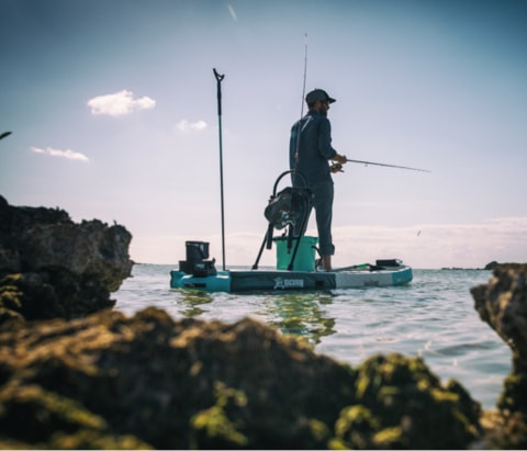 Man fishing from his decked out BOTE Rackham Aero inflatable paddle board.
