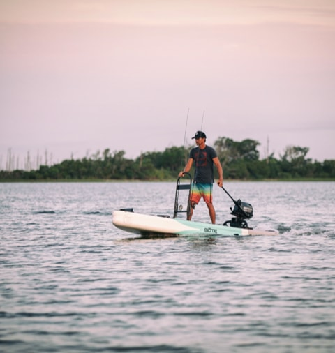 Man driving the BOTE Rover Aero inflatable microskiff and paddle board.