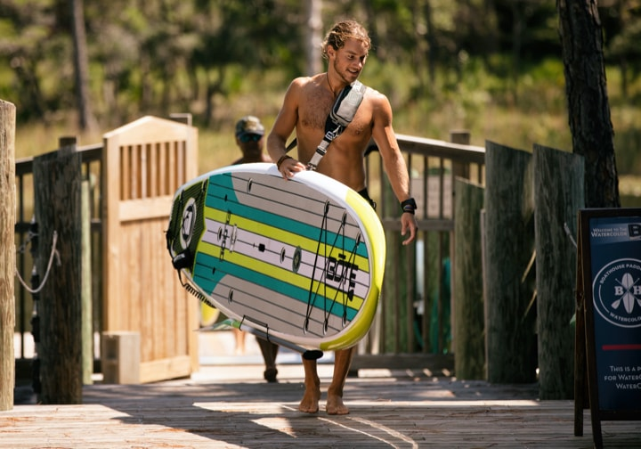 Man carrying his BOTE Gatorshell Flood stand up paddle board with his hands free Travelink™ Sling