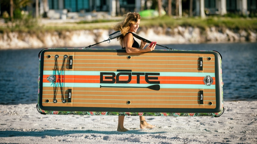 Girl carrying her BOTE inflatable Dock FX hands free with her Travelink™ Sling