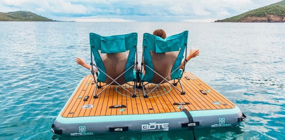 Couple sitting on BOTE inflatable swim platform, the Dock 7 with lake and mountains landscape. Photo by Karma Yachting