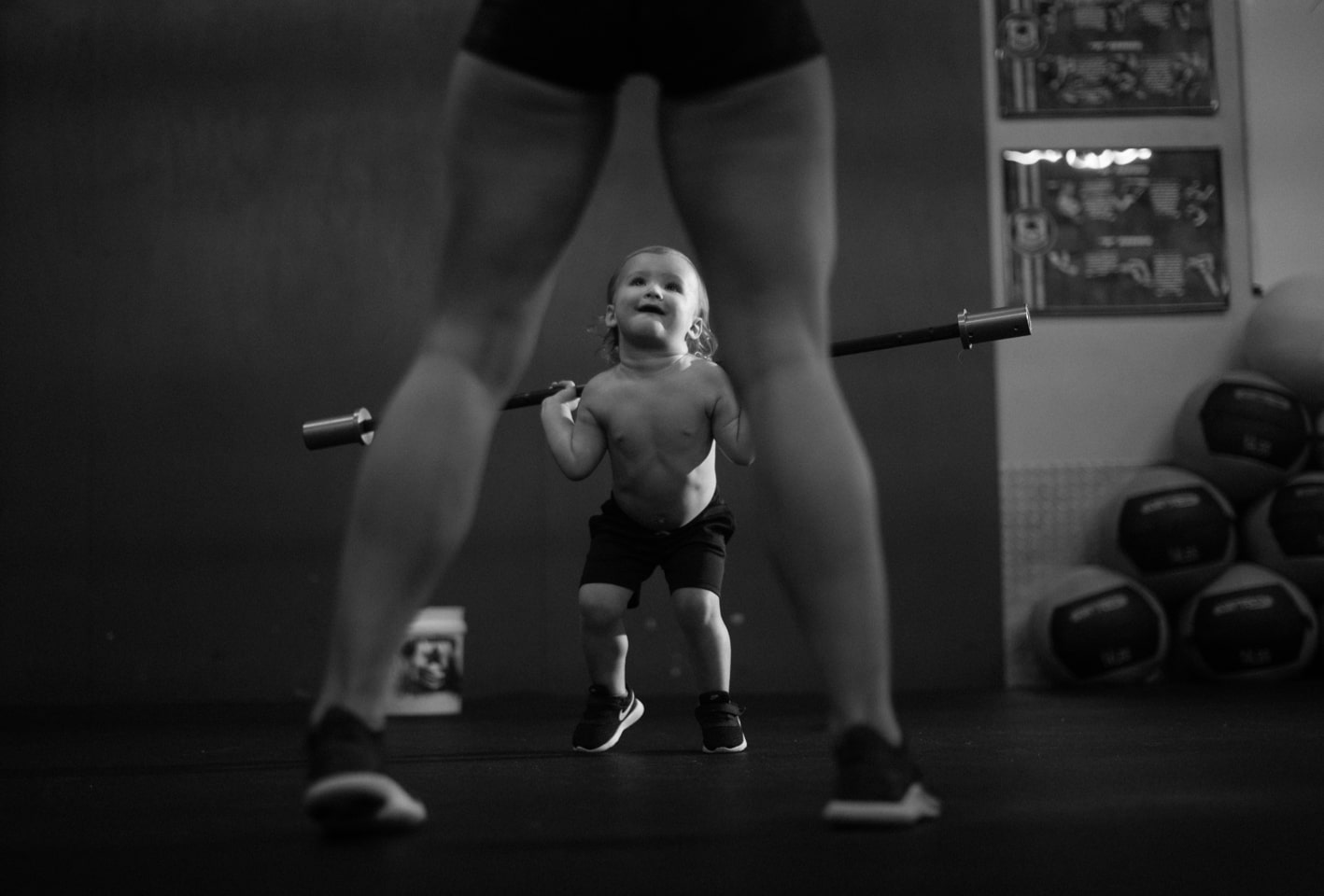 Boy child admiring mom doing barbell squats