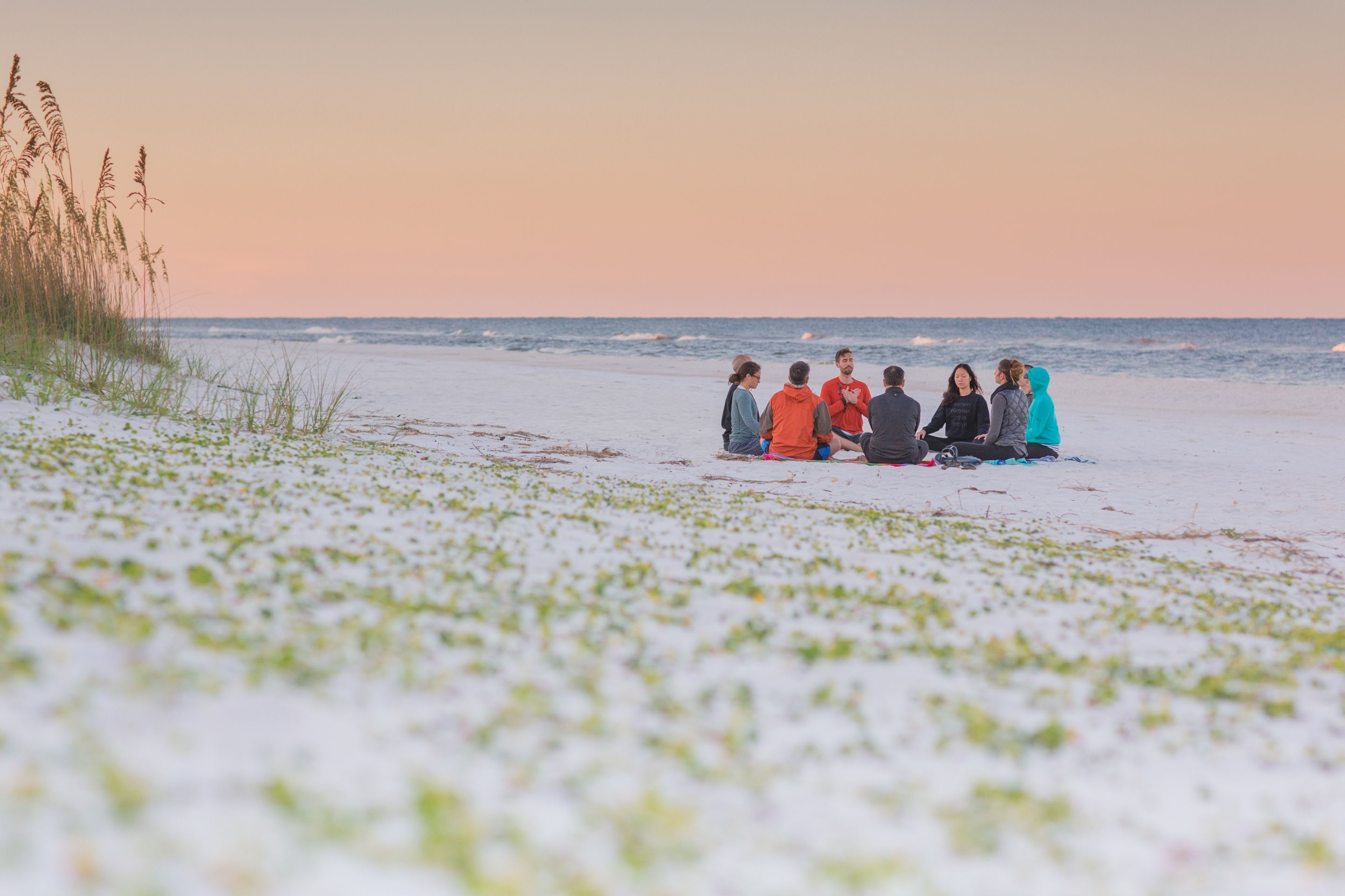 yoga group meditating on beach