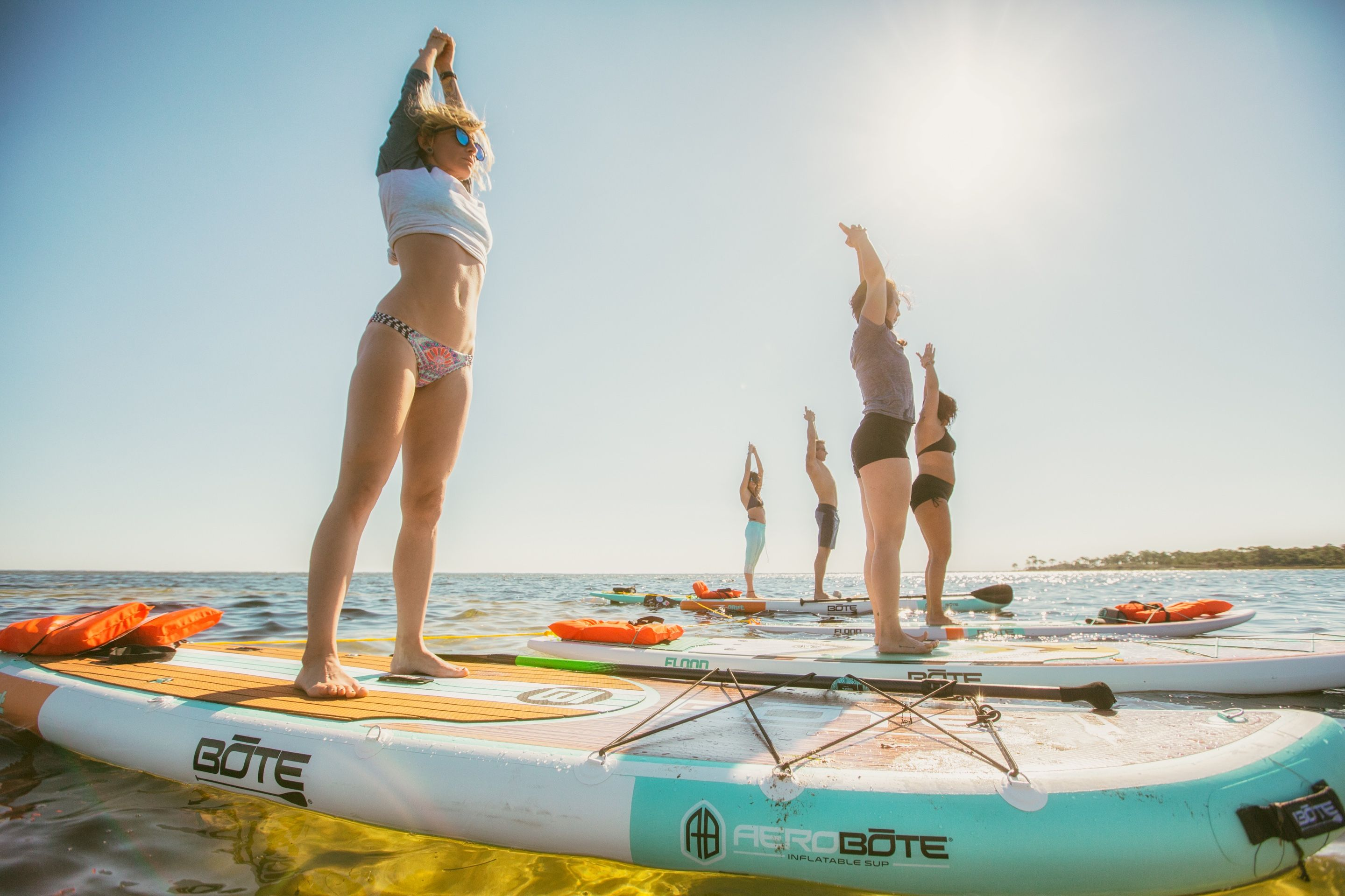 group doing yoga on BOTE inflatable paddle boards