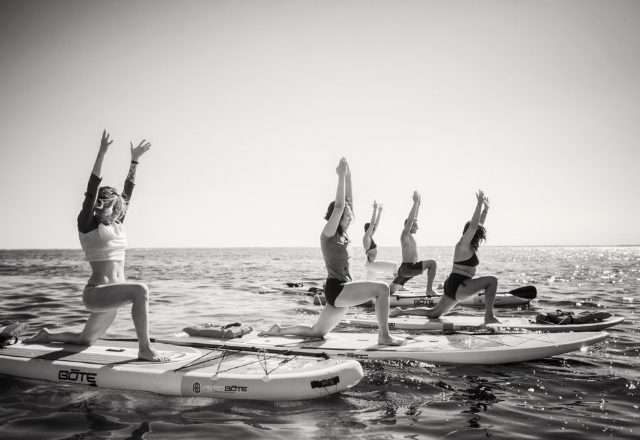 group doing yoga lunge on BOTE inflatable paddle boards