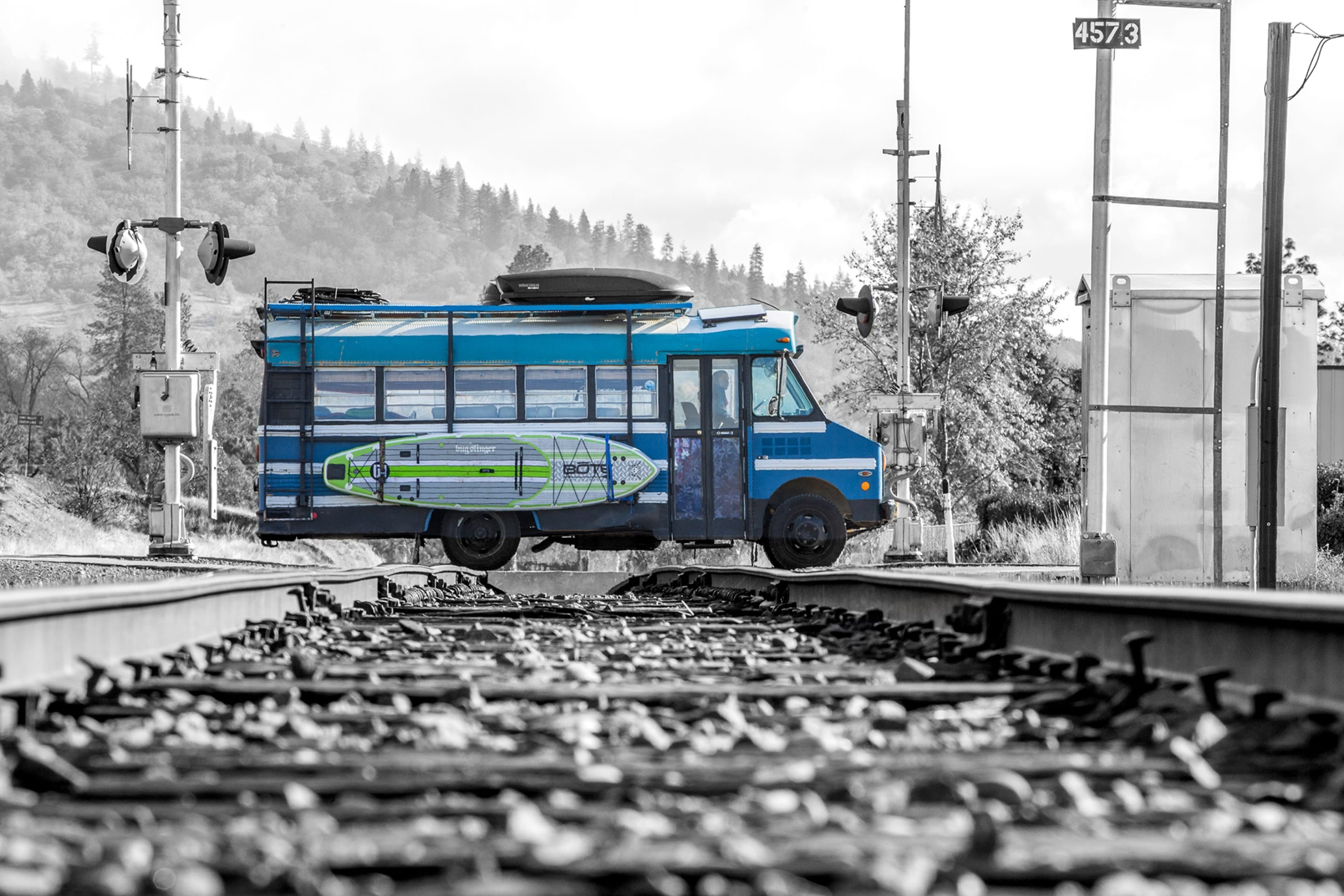 blue bus crossing railroad tracks with BOTE paddle board on the side