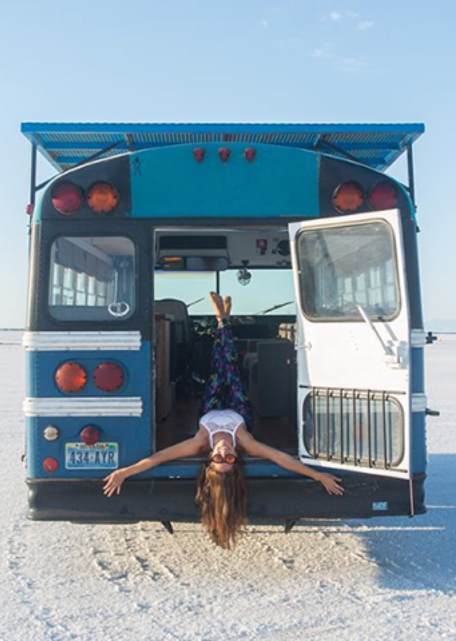 woman hanging out of blue bus