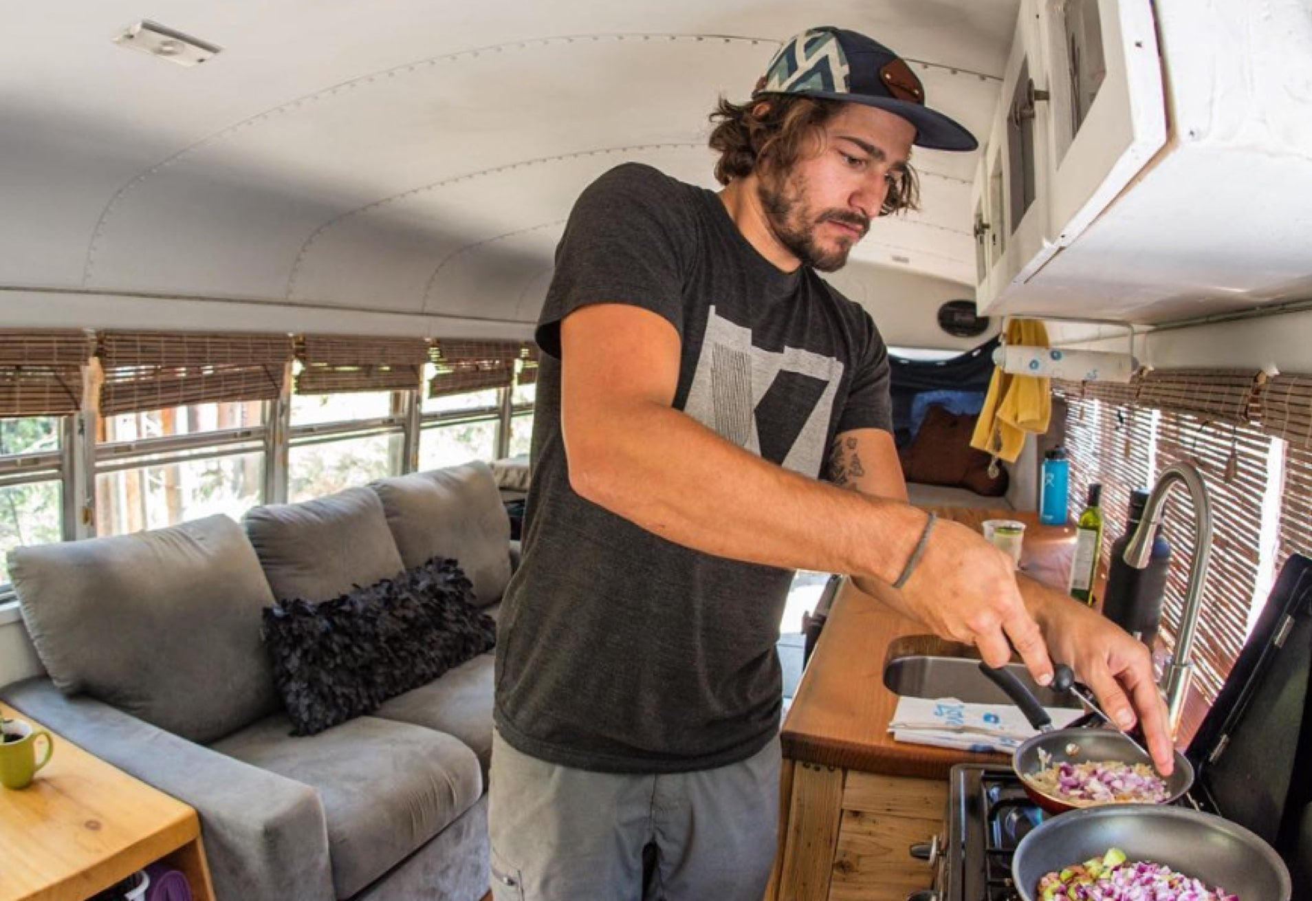 guy cooking in tiny bus home