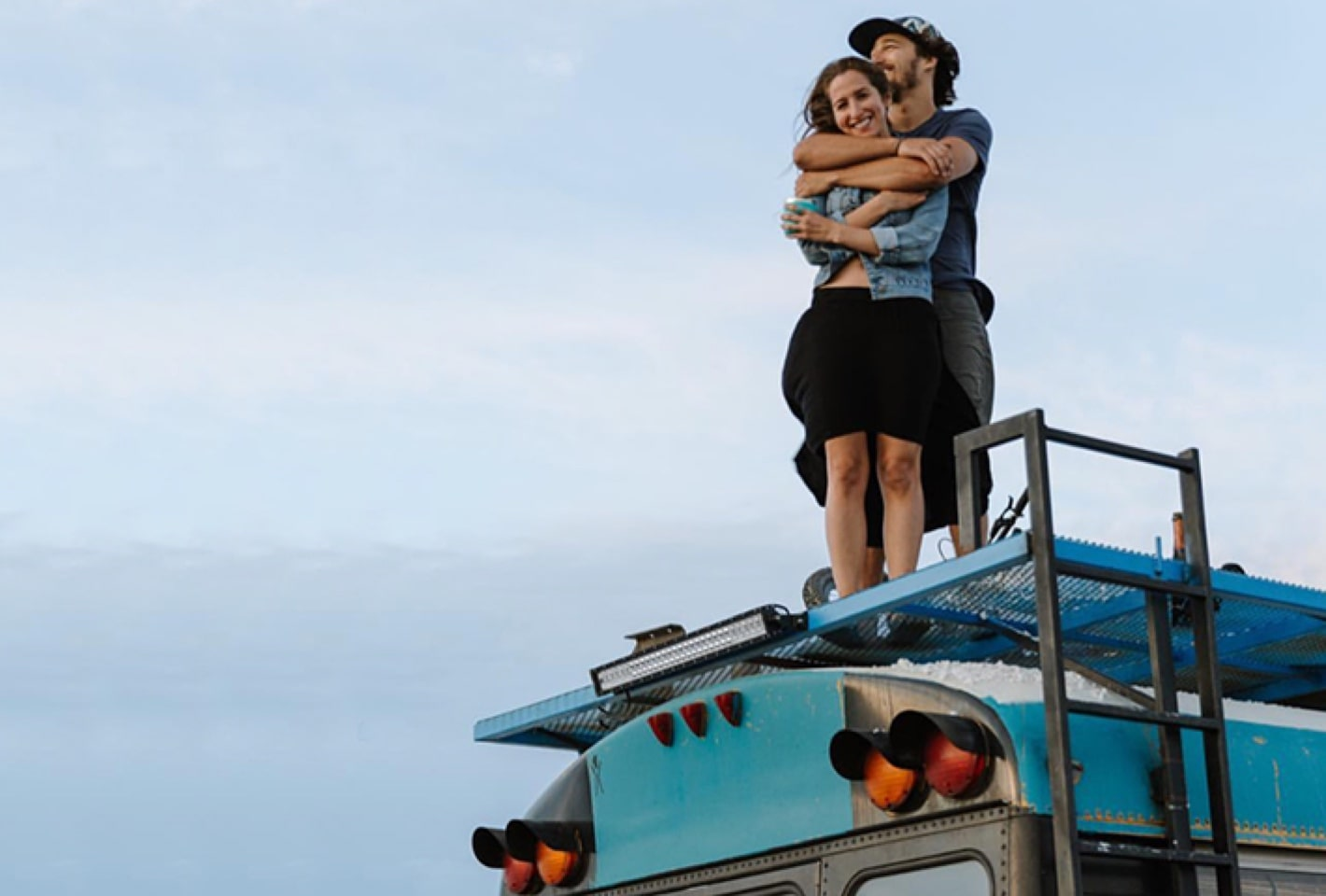 couple on top of blue bus
