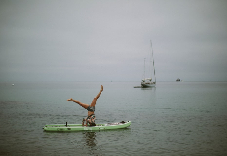 Erin does head stand yoga pose on BOTE inflatable paddle board