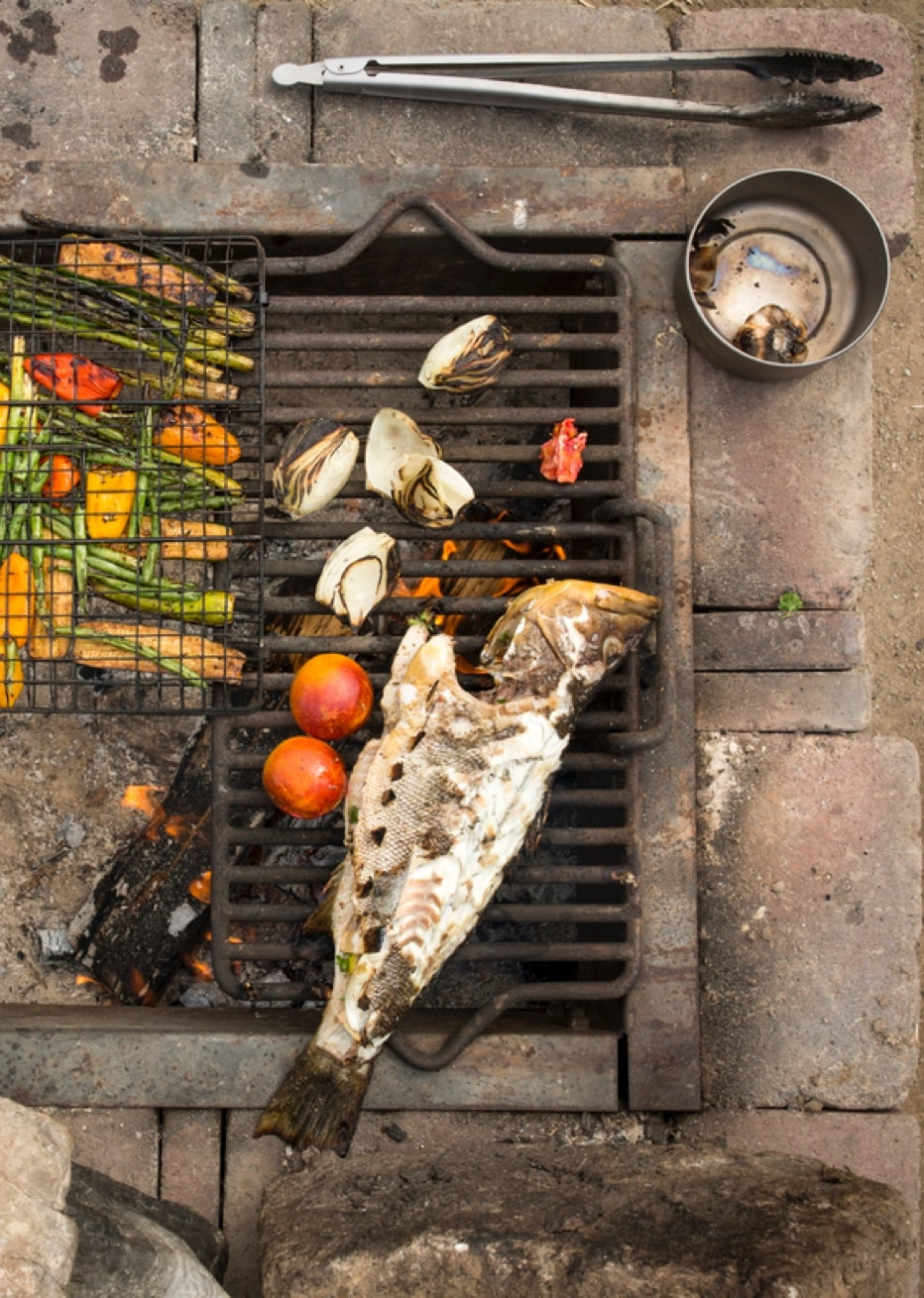 Fish being grilled at campsite along with veggies