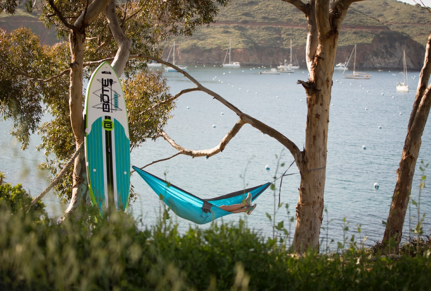 Erin lounging in hammock next to her BOTE inflatable paddle board