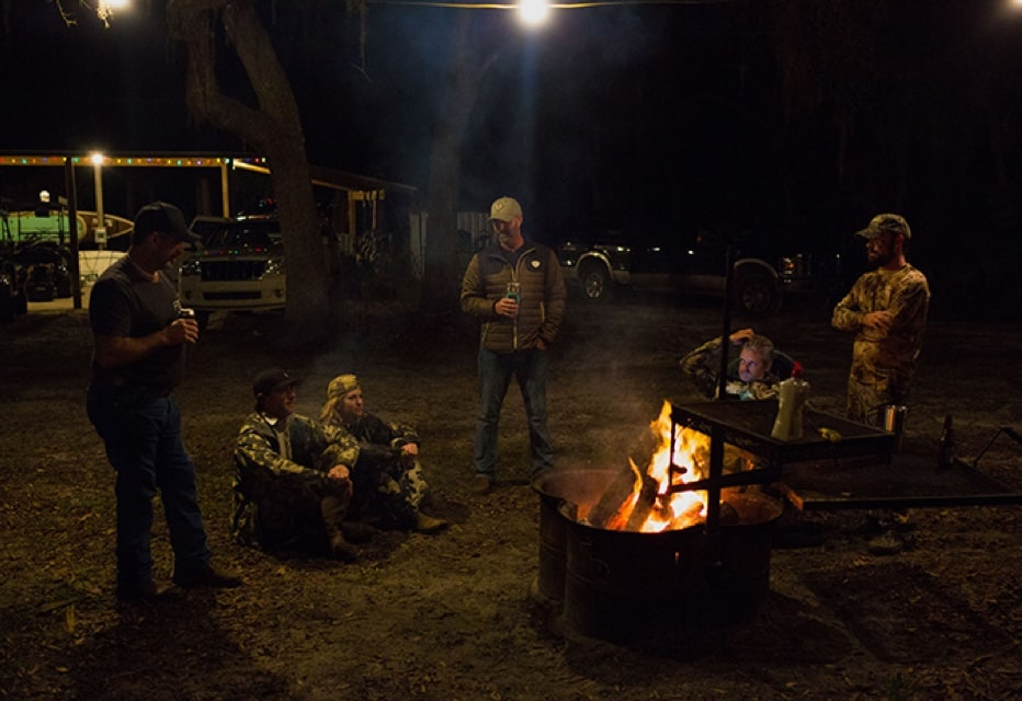 friends drinking beer around a campfire