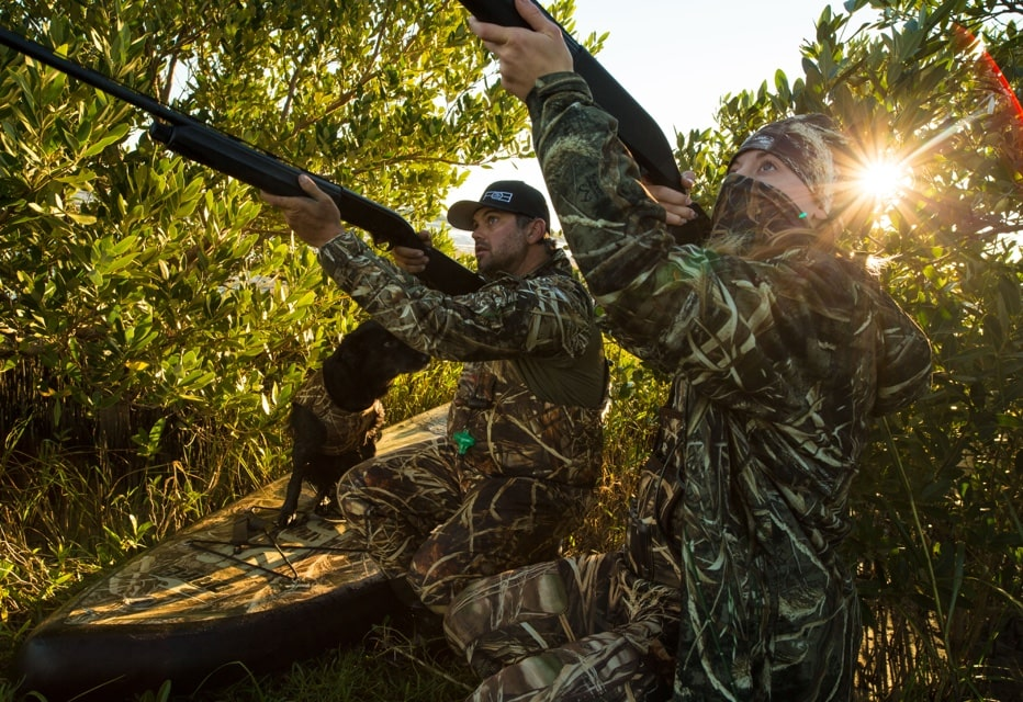 two people duck hunting in camo