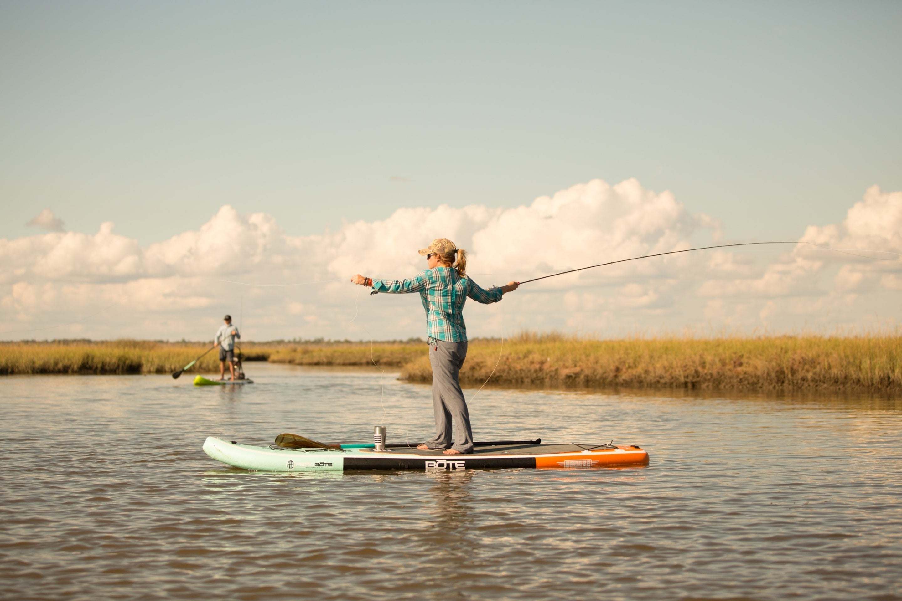 woman fly fishing off BOTE inflatable paddle board