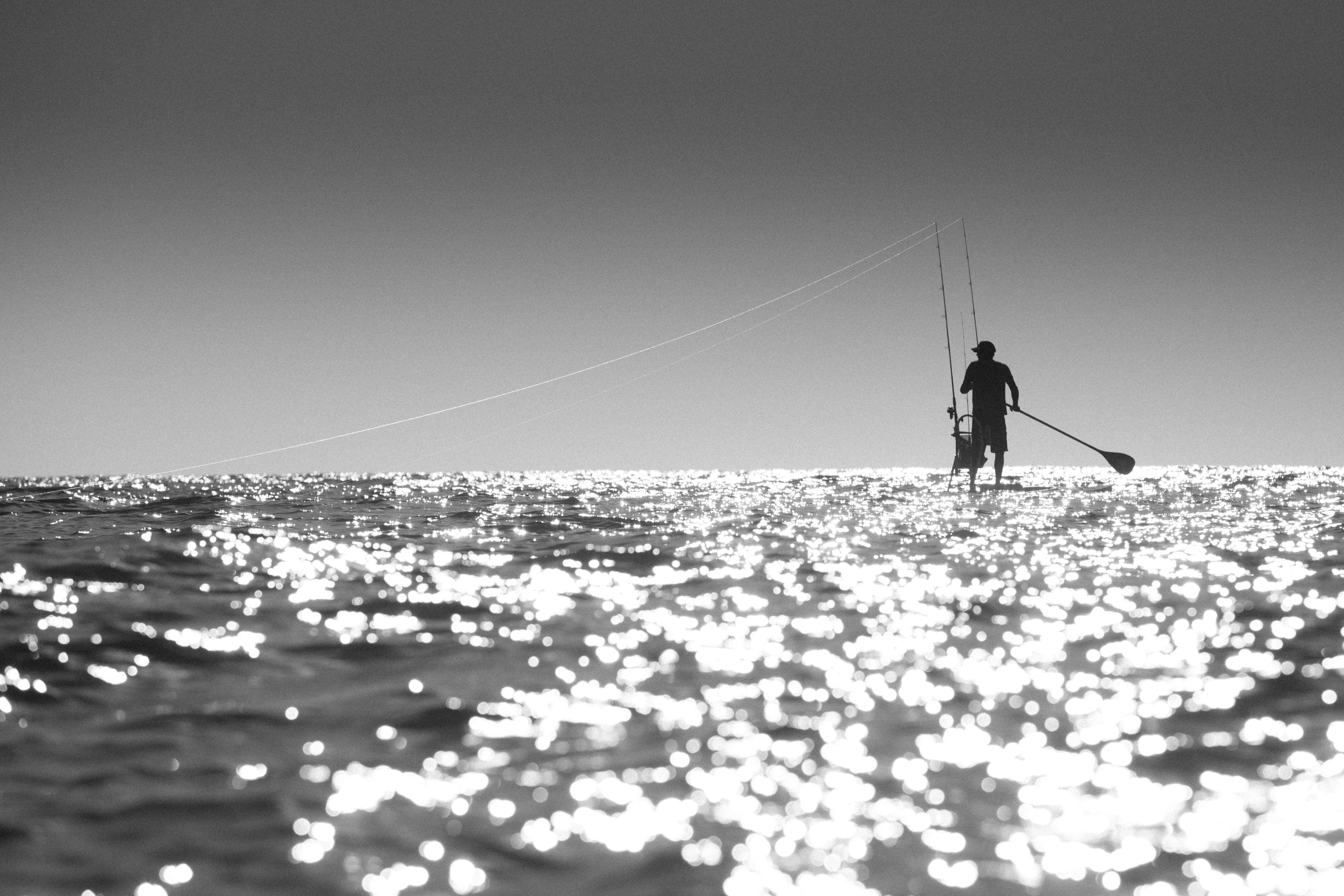 Man fishing in gulf from a BOTE Rackham paddle board