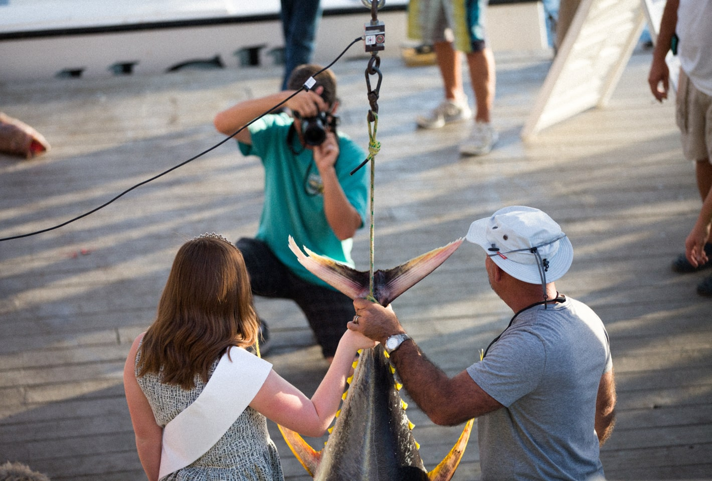 Couple being photographed with freshly caught yellow fin tuna