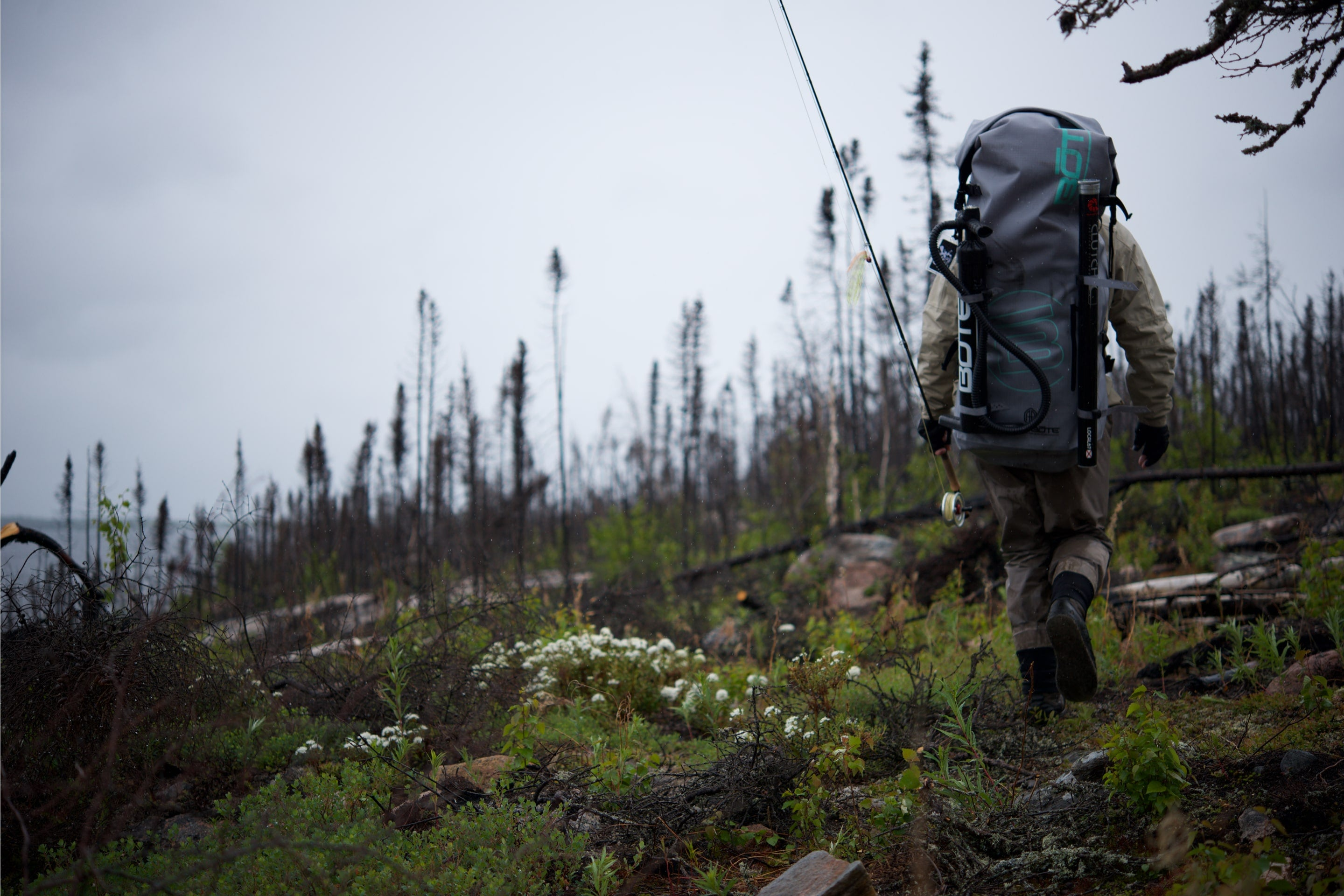 Rob McAbee treks through woods while wearing a BOTE inflatable paddle board backpack