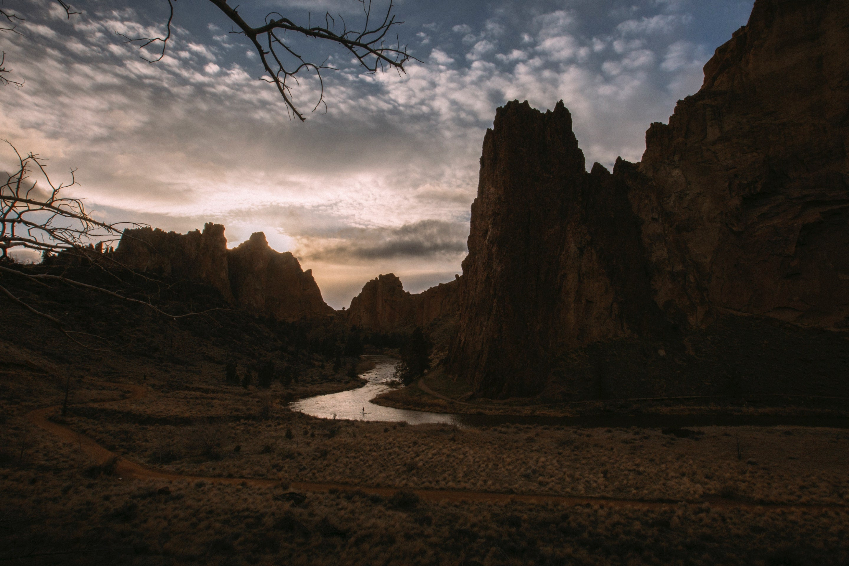 Landond paddling down Crooked River on his inflatable paddle board through Smith Rock State Park, Terrebonne, Oregon