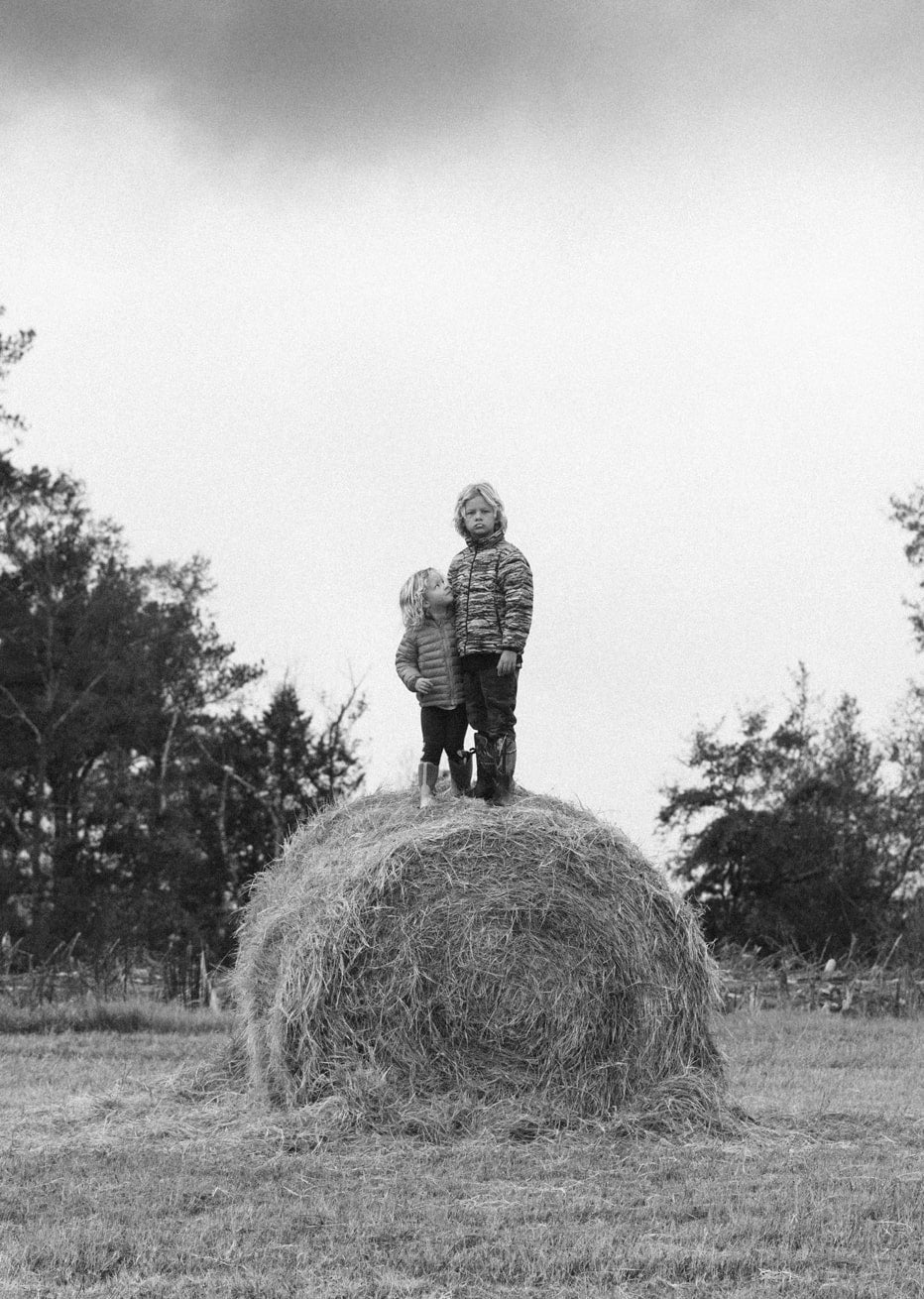 Kids standing on hay bail