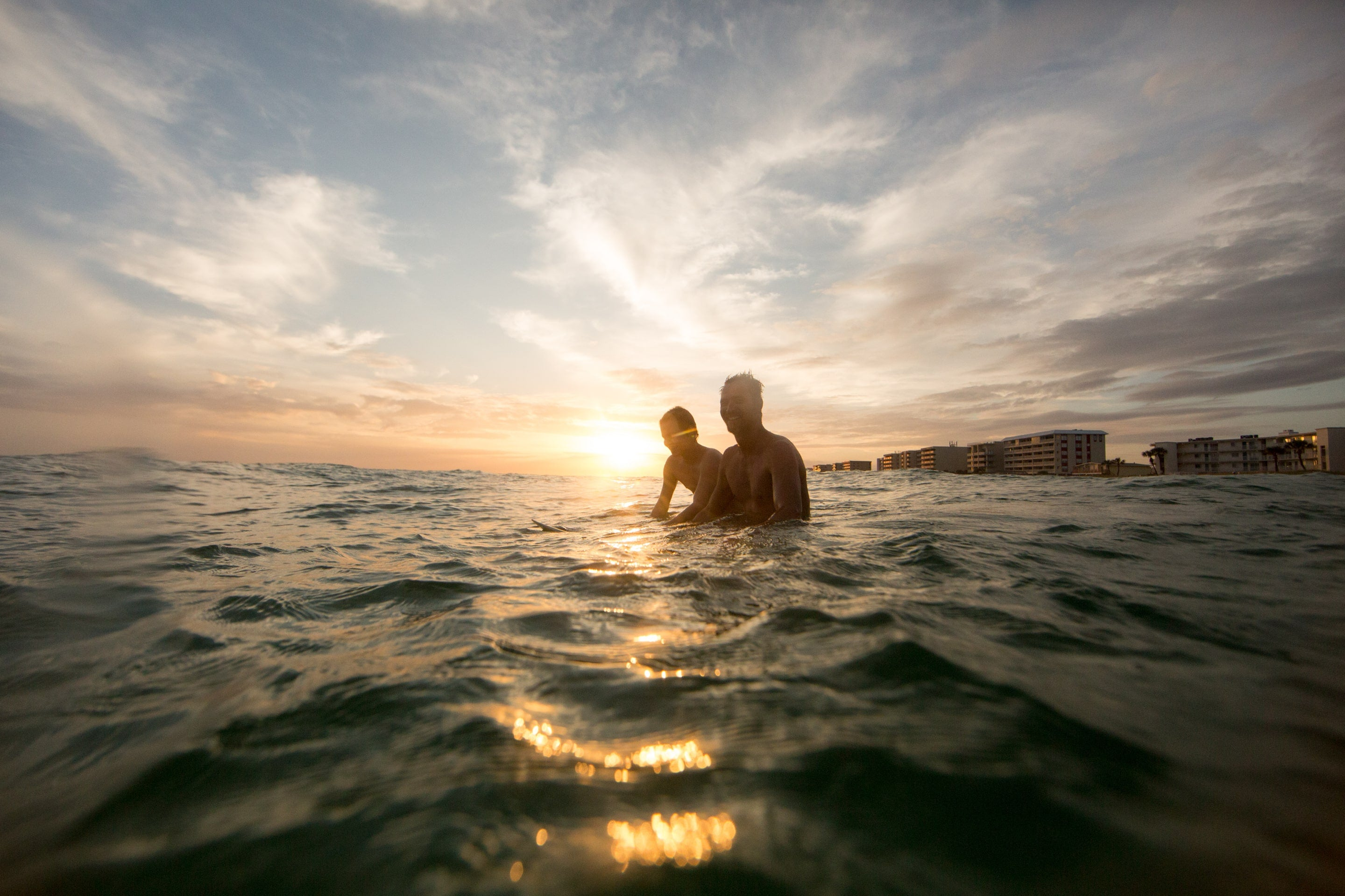 Two Guys on Surfboards at Sunset