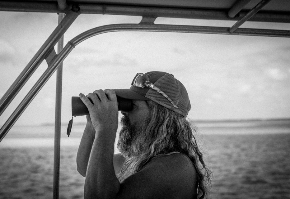 guy using binoculars offshore