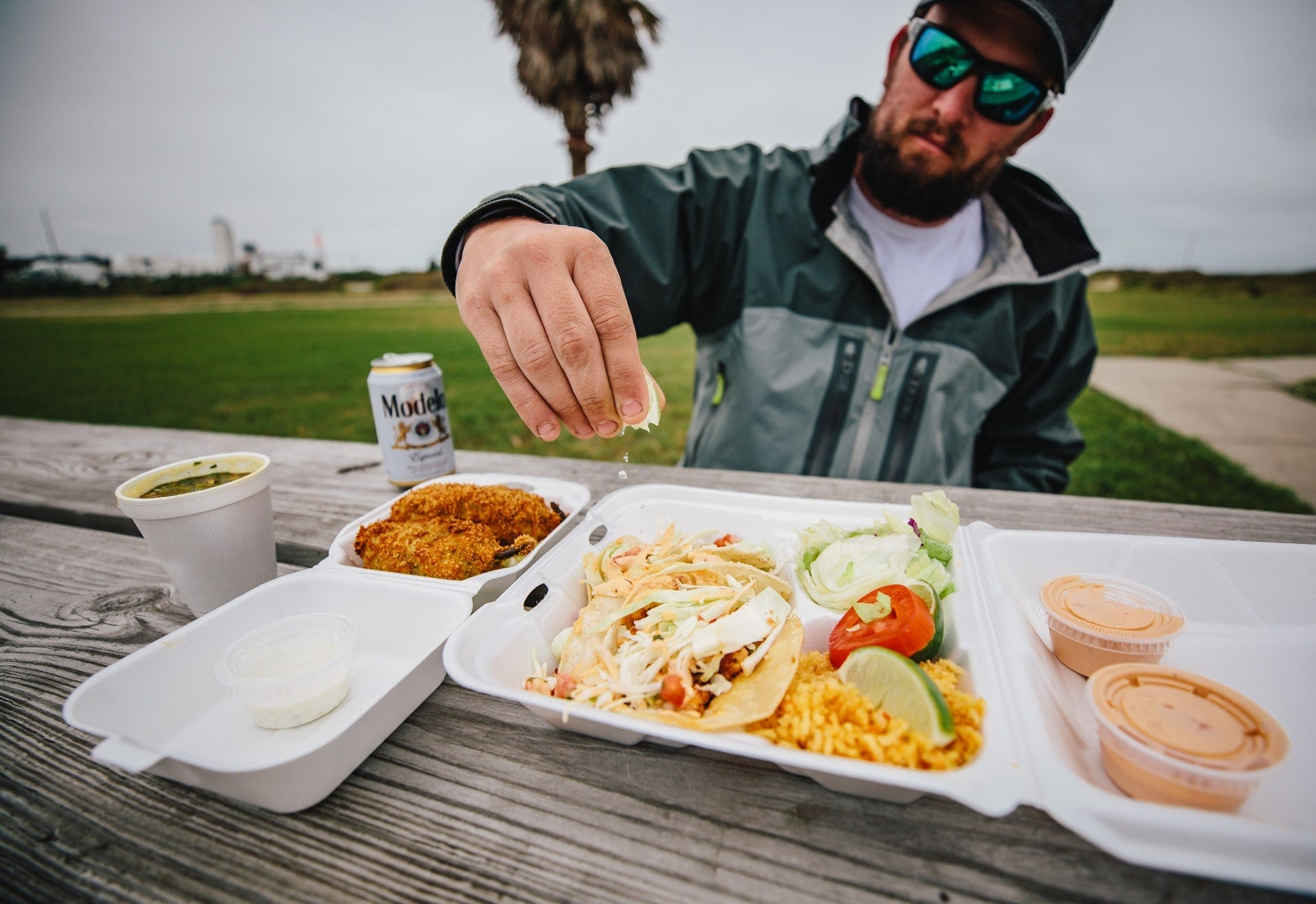 guy squeezing lime on fresh fish tacos