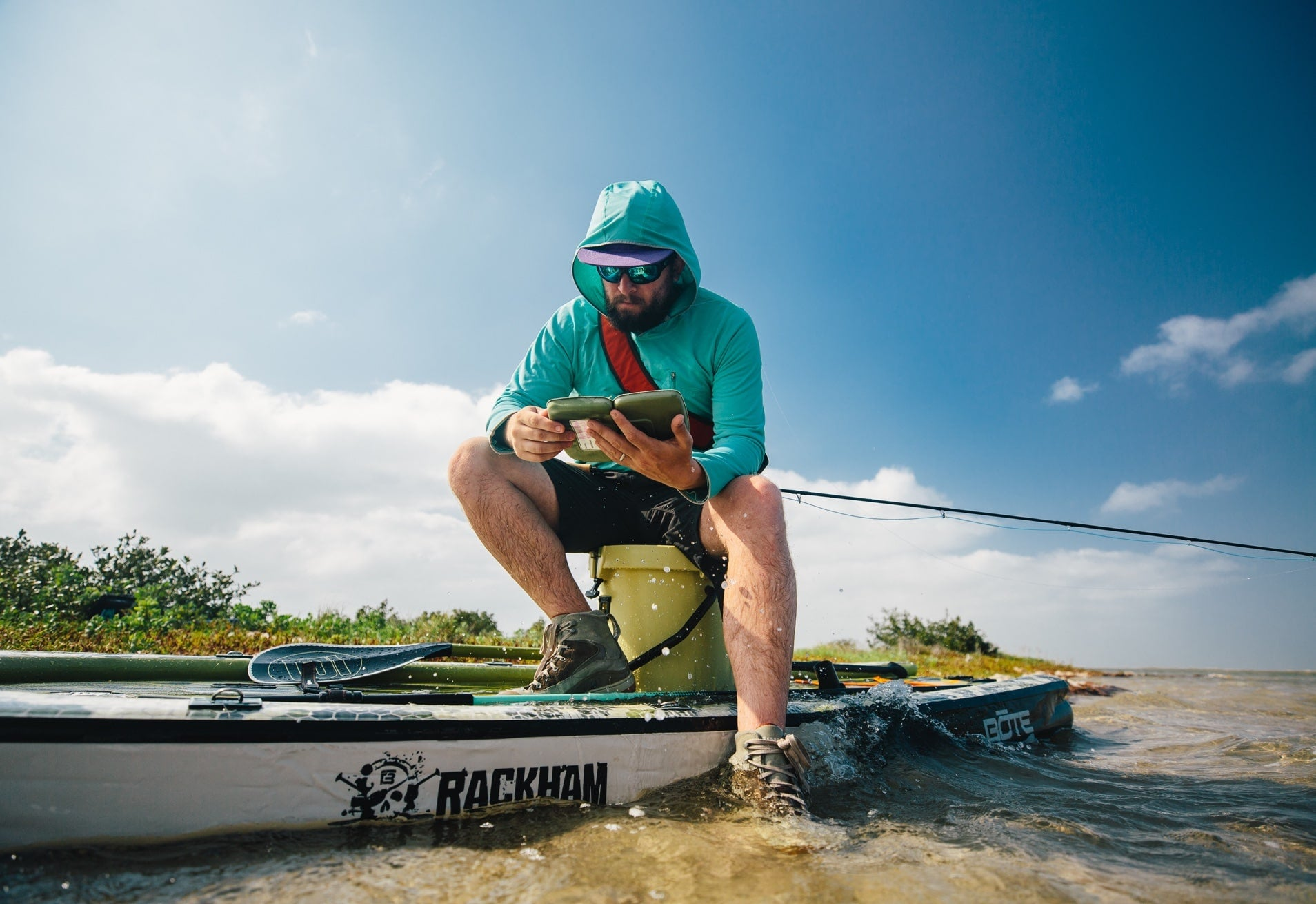 man choosing fly for fishing on BOTE inflatable rackham paddle board