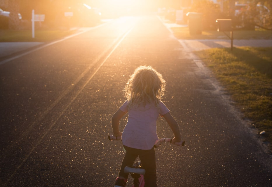 kid biking into sunset